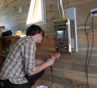Christopher Smith from the film TINY installing his Dickinson in his  Colorado tiny home. Photo credit here. - Off-Grid Heating: Propane VS. Wood Burning - Tumbleweed Houses